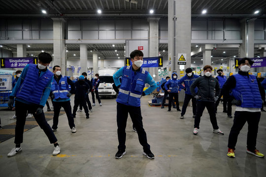 A delivery man for Coupang Jung Im-hong wearing a mask to prevent contracting the coronavirus, warms up before leaving to deliver packages in Incheon