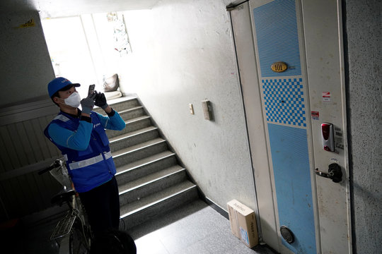 A delivery man for Coupang Jung Im-hong wearing a mask to prevent contracting the coronavirus, takes photographs of a package after delivering in Incheon