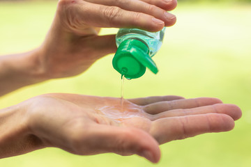 Person disinfecting hands with hand sanitizer. Body care and hygiene concept.