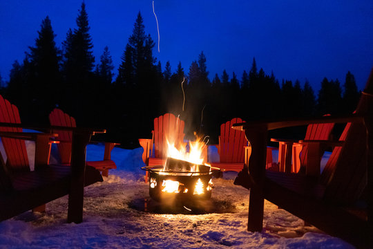 Cozy/romantic evening scene of warming bonfire on snow in winter with red chairs around. Canadian symbols of bear, paw and tree on the fire container. Banff National Park, Alberta, Canada