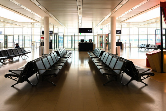 Rows of empty seats in a desserted flight departure gate waiting room on an international airport.