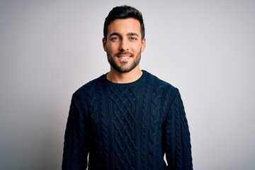 Young handsome man with beard wearing casual sweater standing over white background with a happy and cool smile on face. Lucky person.