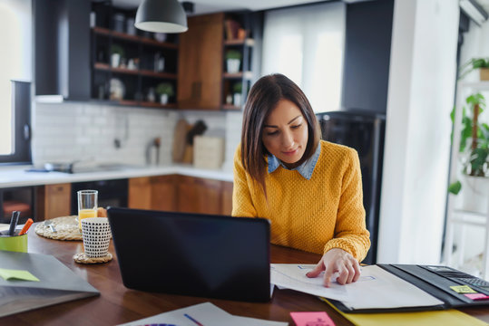 Young business entrepreneur woman working at home while having breakfast