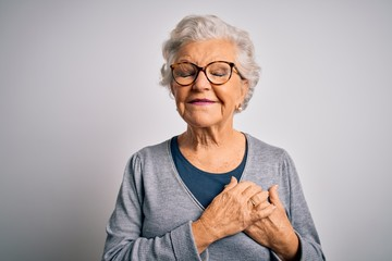 Senior beautiful grey-haired woman wearing casual sweater and glasses over white background smiling with hands on chest with closed eyes and grateful gesture on face. Health concept.