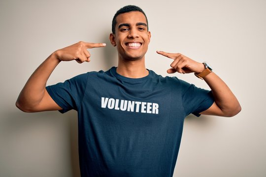 Young handsome african american man volunteering wearing t-shirt with volunteer message smiling cheerful showing and pointing with fingers teeth and mouth. Dental health concept.