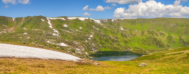 Fototapete - Spring in the mountains. Snow on the slopes, green meadows, lake. Panoramic view.