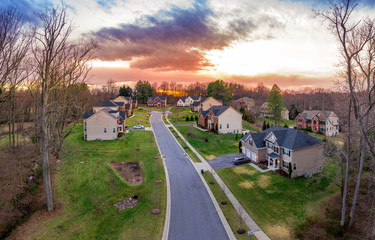 Aerial panorama of luxury mansion type single family homes with landscaping  curb appeal , neighborhood cul-de-sac street American real estate in Maryland USA with dramatic colorful sunset sky