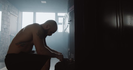 Exhausted young shirtless man sitting alone in dark gym locker room feeling sad after failure day. Good fighting spirit.