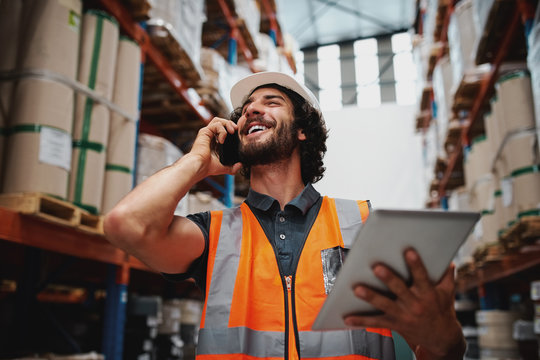 Low angle view of cheerful warehouse supervisor using phone for communication holding digital tablet wearing hardhat and safety vest