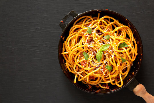 Tasty Homemade Bucatini all Amatriciana Pasta in a cast iron pan on a black wooden background, top view. Flat lay, overhead. Copy space.