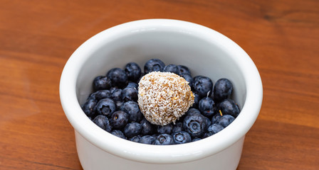 Date ball on blueberries in white bowl on the table