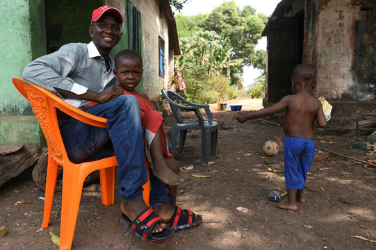 Former mine worker Abdulai Bangura smiles as he sits with his children in front of his family house at Labor Camp community in Lunsar