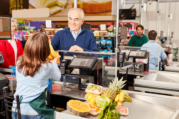 Customer at the supermarket cashier pays for fruit