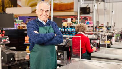 Senior as a cashier at the supermarket cashier