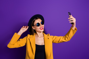 Fototapete - Turned photo of cheerful lovely cute girl travel video blogging make selfie on multimedia device cellphone touch her velvet hat wear good look outfit isolated over purple color background