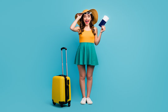 Full body photo of pretty lady traveler hold passport tickets rolling suitcase luggage airport cheap flights wear sun specs short summer dress headwear shoes isolated blue background