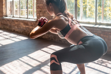 Closeup young sporty woman fitness trainer do bodyweight squats practice squatting exercise with hands clasped bending forward keep fit in modern gym wooden floor healthy lifestyle concept copy space.
