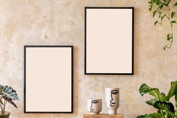 Interior design of living room with two black mock up poster frames, shelf, vases, plants and elegant personal accessoreis. Grunge wall. Stylish home decor. Wabi sabi concept.Template.