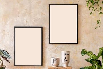 Interior design of living room with two black mock up poster frames, shelf, vases, plants and...