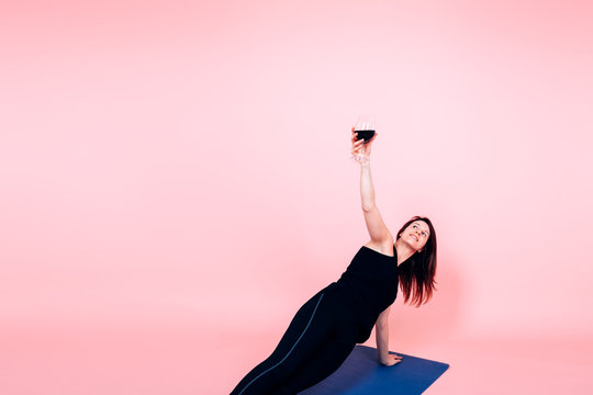 young woman holding a glass of red wine while performing yoga - wine and yoga trend concept