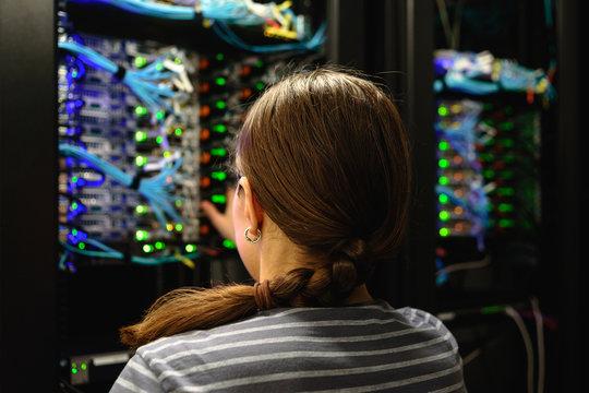 Woman networking engineer near working server rack