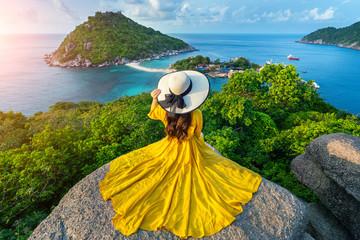 Wall Mural - Beautiful girl sitting on viewpoint at Koh Nangyuan island near Koh Tao island, Surat Thaini in Thailand.