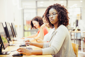 African American adult student working in computer class. Line of man and women in casual sitting...