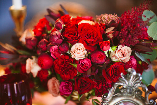 Floral arrangement with red and pink roses is on the table
