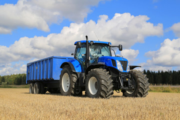 New Holland T7.250 Tractor and Agricultural Trailer on Field. Illustrative Editorial Content.