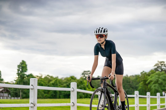 asian female bicyclist cycling pass a farm, standing up on the bicycle looking forward, riding a black bicycle wearing bike helmet and goggles, with grey clouds covering the sky and tall green trees.