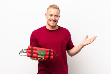 Poster Palm tree young blonde man smiling cheerfully, feeling happy and showing a concept in copy space with palm of hand against white wall holding a dynamite explosive
