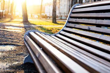 Wooden brown bench with a back in the Park against the background of a bright sunset.
