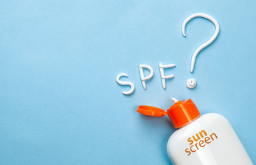 Sunscreen. Cream in the form of question mark and the inscription SPF on blue background with white tube. Concept of how to choose sunblock