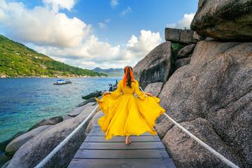 Wall Mural - Beautiful girl running on wooden path at Koh Nang yuan island near Koh Tao island, Surat Thani in Thailand.