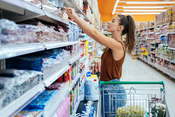 I will take this one stock photo. Young smiling woman shopping in local supermarket. She is choosing product from shelf.