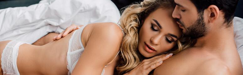 Panoramic shot of beautiful woman touching chest of muscular boyfriend on bed Fotobehang