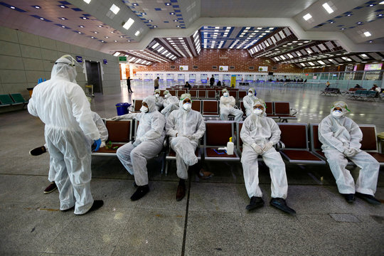 Iraqi medical staff rest after checking passengers' temperature, amid coronavirus outbreak, at Najaf airport