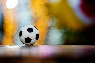 The soccer ball is placed on a wooden floor and has a blurred background with beautiful bokeh.