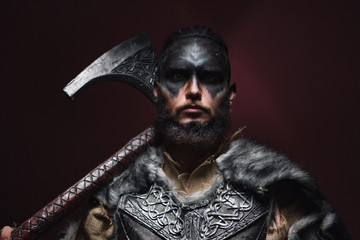 portrait of a Viking man with an axe. A man of 30 years holds a large battle axe on his shoulder. Warrior dressed in an authentic suit Wall mural