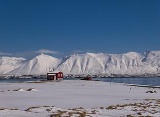 Rotes Haus an der Küste vor verschneiten Bergen