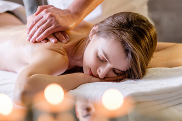 Young handsome male professional massage therapist does massage to a beautiful young girl lying on a couch in a spa salon. Caucasian woman treats back pain. Beauty and body care concept Fotomurales
