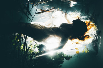 Silhouette underwater girl with long hair. Swimming Mermaid.