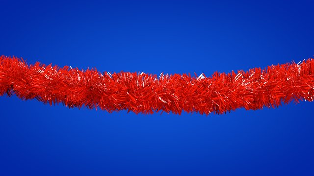 Red christmas tinsel  on blue background