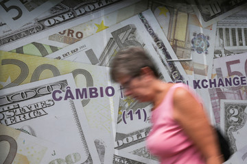 A woman passes by the facade of a currency exchange office decorated with images of dollars and euro bills, in Sao Paulo