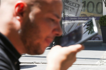 A man passes by the facade of a currency exchange office decorated with images of dollars and euro bills, in Sao Paulo