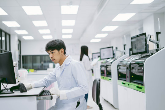 young male scientist looking results  from automation blood analyzer report in computer and young female scientist working with automation blood analyzer at  medical laboratory