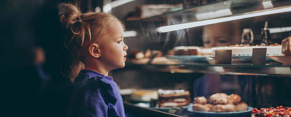 lovely girl admiringly examines a lighted showcase with various delicious cakes and desserts