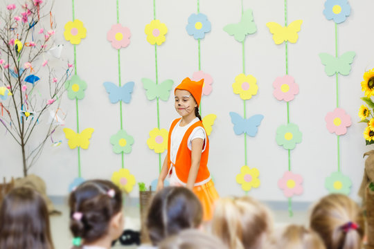 young actress in a fox costume speaking in front of children