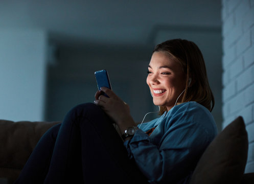 girl smartphone mobile phone night smiling earphones texting late glowing screen