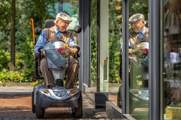 An elderly person on an electric vehicle looks into a shop window